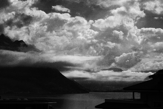Black and white clouds over mountains and a lake.